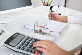 Close-up Of Businessperson Calculating Budget With Calculator At Desk poster