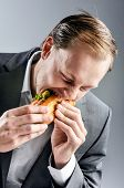 Hungry man in business suit devours BLT baguette with big greedy bite poster