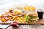 fast food and unhealthy eating concept - close up of hamburger or cheeseburger, deep-fried squid rings, french fries, drink and ketchup on wooden table poster