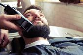barber shaving beard with electric razor in vintage barber shop poster