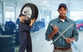 Smiling repairman with tire wrench in car repair service. poster