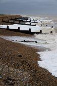 Stormy stony beach waves crashing with Groynes groins. Winchelsea Beach Winchelsea Beach Hastings Kent England United Kingdom. poster