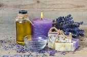 Spa lavender concept. Lavender oil lavender flowers handmade soap and sea salt with burning aromatherapy candle. poster