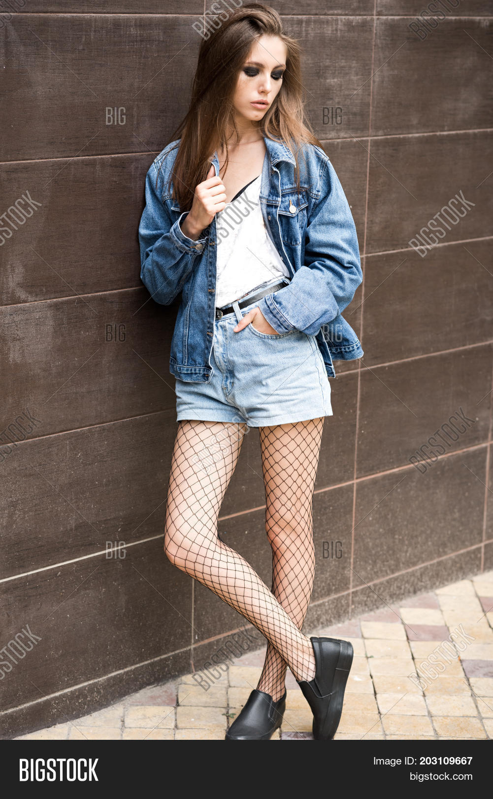 08ad1cd67c3 Beautiful girl in denim shorts and jeans jacket in the street. Rock style.  Fashionable