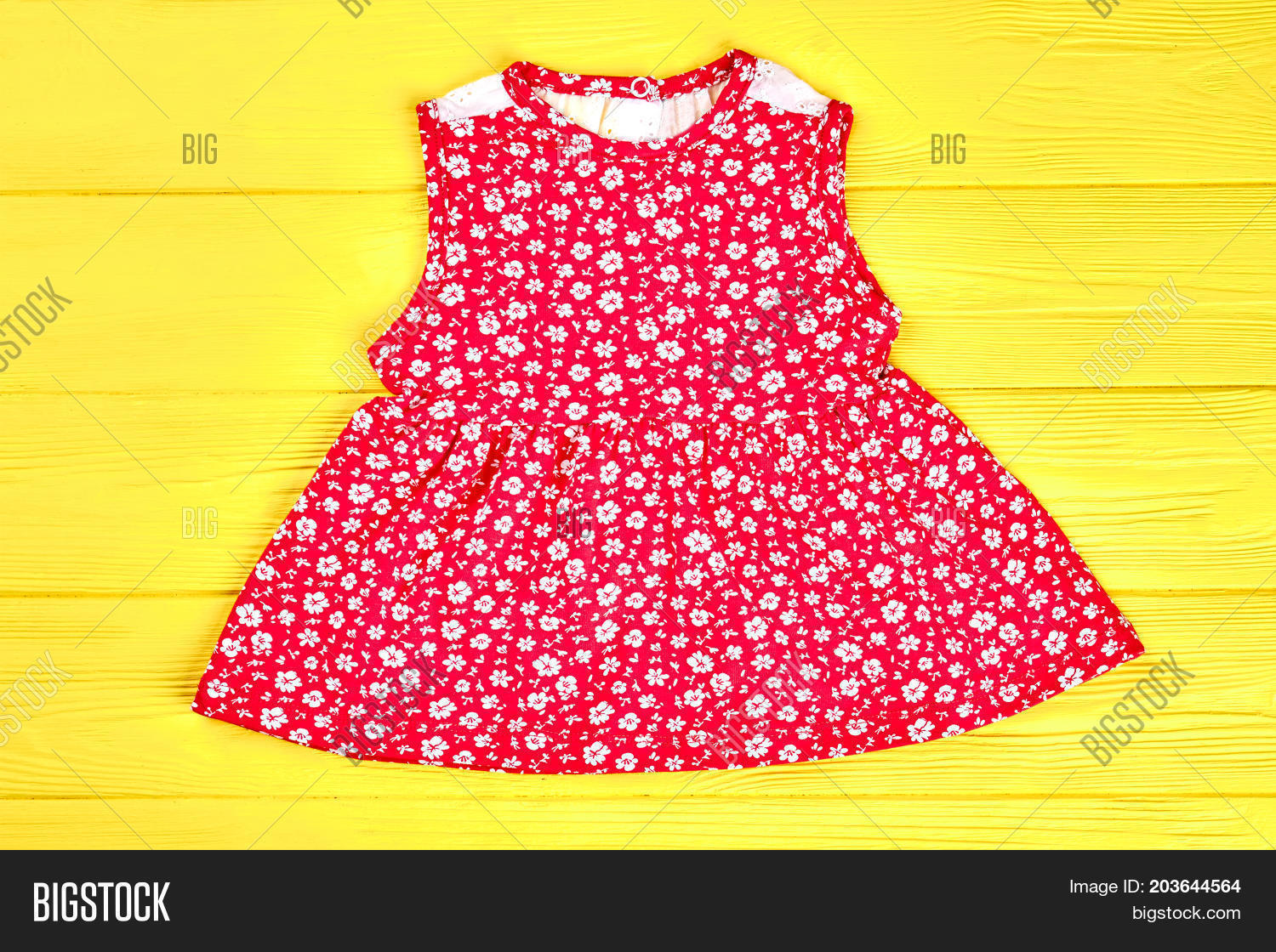 4dfcec1ed5264 Little girls red patterned top. Baby-girl red natural printed dress on  yellow wooden