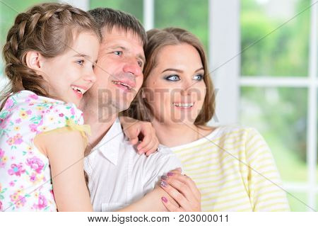 Close up portrait of cute little girl posing with  her parents
