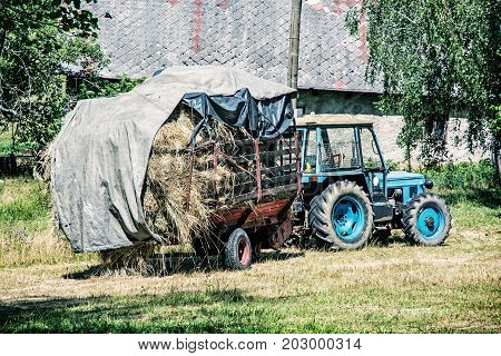 Old tractor with hay. Agricultural scene. Seasonal rural scene. Blue photo filter.