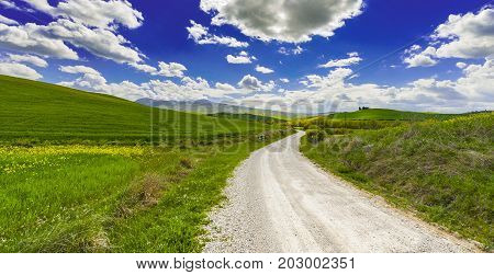 Italian landscape with dirt road between meadow early in the spring. Agriculture in Italy fields and pastures.