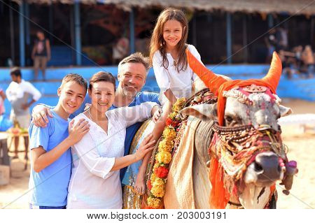 Cute little girl in white dress sitting on bull, family standing nearby