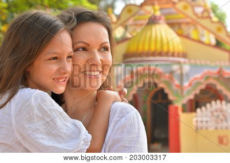 Mother hugging her cute little daughter with blurred mosque on background