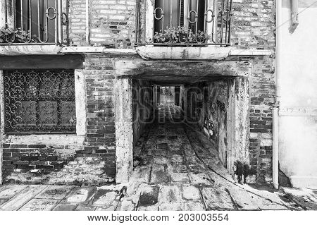 Narrow passage between old houses in Venice. Street with archway in the medieval italian town. Black and white picture