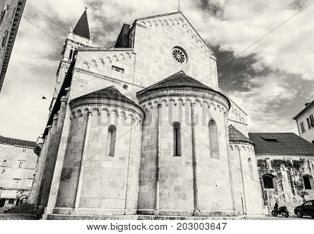 The Cathedral of St. Lawrence is a roman catholic triple-naved basilica constructed in romanesque-gothic in Trogir Croatia. Religious architecture. Black and white photo.