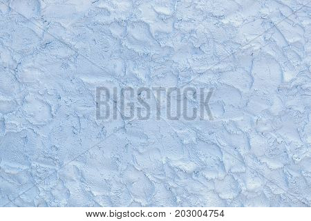 Light blue surface made of the rough brushworks of plaster as a background