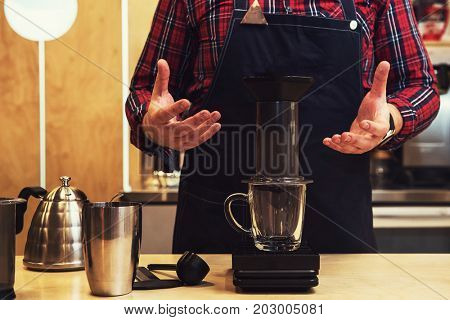 Barista brewing coffee in aeropress in the cafe