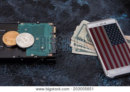 Bitcoin coin on HDD with smartphone with USA flag