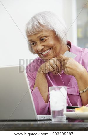 African American woman using credit card to shop online