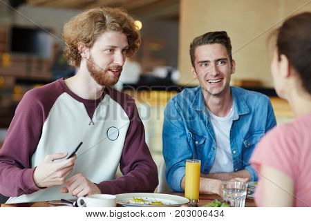Happy guys talking to their groupmate by lunch between classes in college cafe