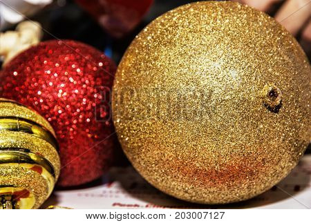Yellow and red shimmering christmas baubles. Symbolic objects. Xmas decoration.