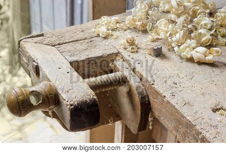 Fragment of old woodworking workbench with two fixing device of workpieces - planing stop and shoulder vise with wooden screw and shavings on workbench