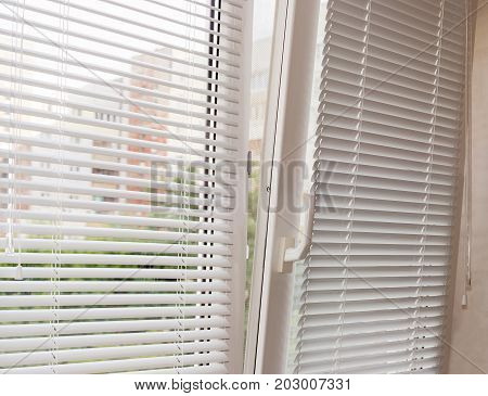 Fragment of the modern tilt and turn plastic window tilted inwards at the top with control handle and white horizontal window blinds