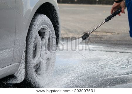 A strong water pressure washes off a thick foam from the wheels of the car