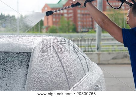 The employee is engaged in washing the car under high pressure