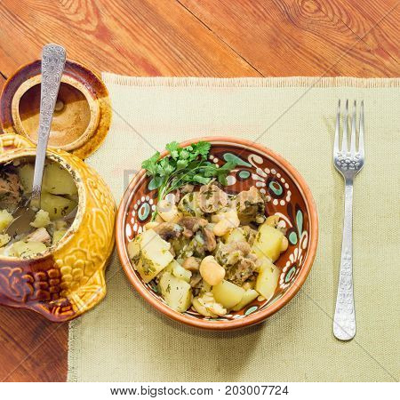 Top view of the Ukrainian version of the dish Chanakhi in a clay bowl and fork on a napkin - potatoes with meat mushrooms and haricot beans baked in a clay pot on wooden surface