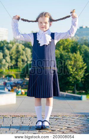 Little girl schoolgirl took up pigtails with her hands