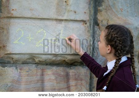 Girl with pigtails wrote a mathematical example on a stone wall. schoolgirl