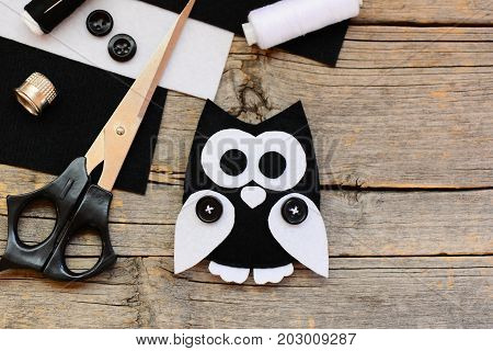 Stuffed felt owl toy, black and white felt sheets, scissors, threads, thimble, black buttons on an wooden background with empty place for text. Beginner sewing projects idea. Top view. Closeup