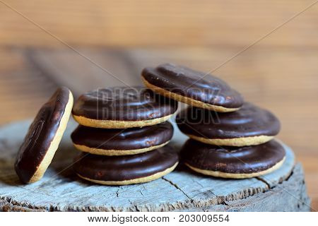 Sweet biscuits pile on a wooden background. Round biscuits in chocolate glaze icing made with cocoa powder. Closeup