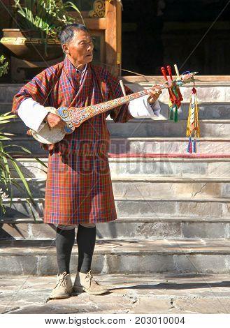 PARO BHUTAN - November10 2012 : Unidentified old man musician in traditional dress (Gho) playing Dramnyen instrument at hotel in Paro Bhutan