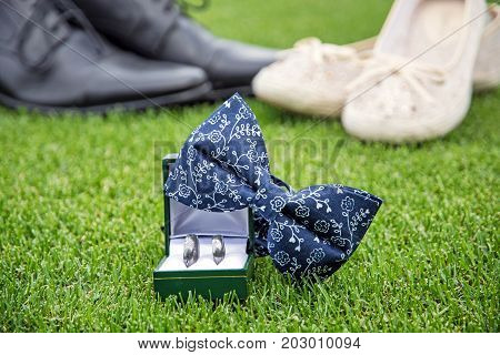 Wedding rings bow tie and women's and men's shoes on the green grass. Symbol of love.