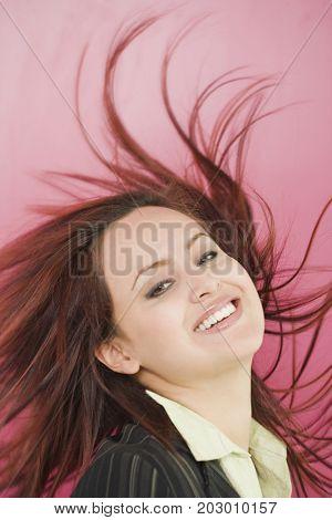 Hispanic woman flipping hair back and smiling