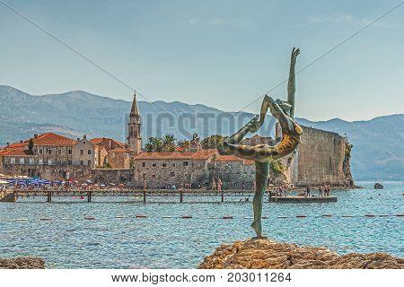 BUDVA, MONTENEGRO - August 18, 2017: Statue of a ballerina in the Arab position. Moghren Beach. Background Blurred Old Town Budva, Montenegro.