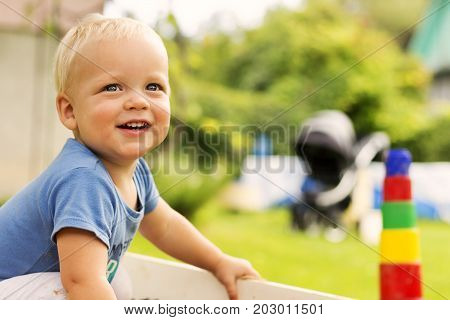 Close-up Portrait Of Cute Smiling Baby Boy On The Blurred Nature Background. Copy Space