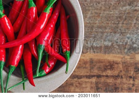Fresh red hot chili pepper in top view or flat lay. Close up of red chili in bowl on wood table with copy space for background or wallpaper. Spicy food : red hot chili pepper fresh vegetable concept. Red hot chili is the one of spicy herb.