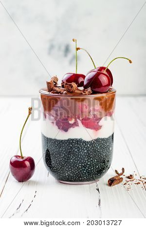 Healthy Black Forest dessert. Black activated charcoal chia pudding with cherries coconut cream and chocolate. Vegan creamy breakfast. Copy space background