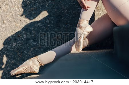 Closeup of ballet dancer sitting outdoors. Ballet dancer wearing pointe shoes sitting on stairs.