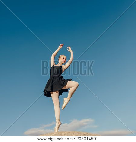 Ballet dancer practicing dance moves outdoors. Female dancer standing on one toe in pointe shoes on a rock with blue sky in the background.