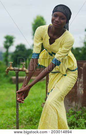 Standing gorgeous African girl washing hands outdoors with clean water - Health and Medicine Symbol