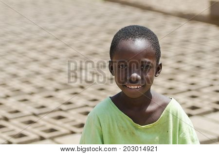 Little African child smiling outdoors behind bricks - Child Labour concept