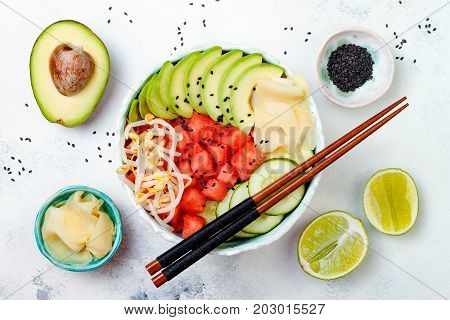 Vegan watermelon poke bowl with avocado cucumber mung bean sprouts and pickled ginger. Top view overhead flat lay