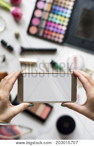 Woman Hands Using Mobile Phone Capture Photo with Cosmetics Background