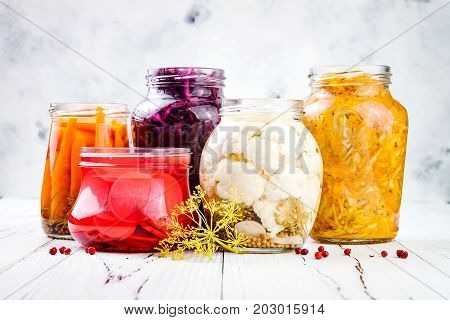 Sauerkraut variety preserving jars. Homemade red cabbage beetroot kraut turmeric yellow kraut marinated cauliflower carrots and radish pickles. Fermented food.