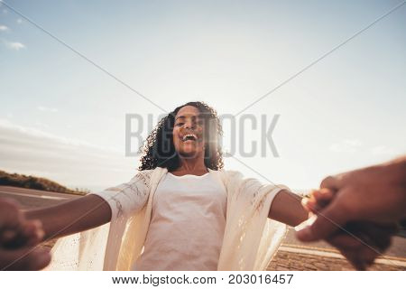 POV shot of smiling african woman spinning with her boyfriend. Laughing female holding hands of her boyfriend and having fun.