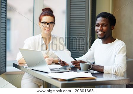 Multi-ethnic team of financial managers posing for photography while sitting at boardroom table and analyzing statistic data, group portrait