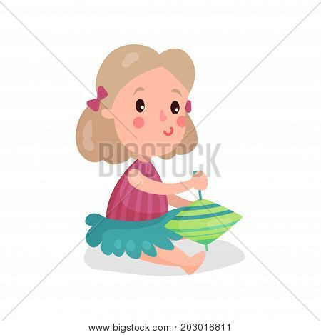Sweet blonde little girl sitting on the floor playing with humming top cartoon vector Illustration on a white background
