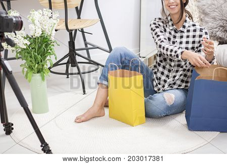 Smiling girl sitting on the floor showing off her shopping during recording vlog with camera at home