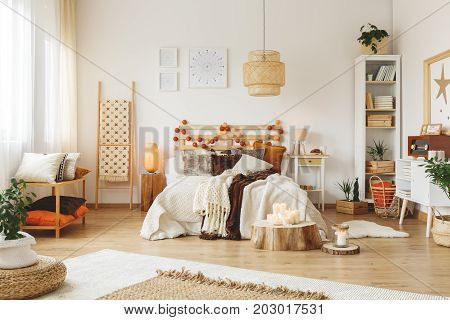Big wooden lampshade hanging in a bright bedroom